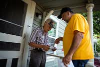"<p><span style=""font-size: 1em; background-color: transparent;"">Community organizer Ronnie Mestas hands a flier to Fernando Gonzalez outside his rent home on McBroom Street in Dallas. (G.J. McCarthy/Staff Photographer)</span></p>"