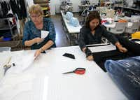 Merri Lester (left), product development engineer, and Ha Vo, sample maker, cut patterns for a prototype suit at the company's headquarters in Dallas. The Design District office includes workshops to make samples of apparel and sunglasses.(Rose Baca/The Dallas Morning News)
