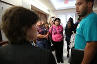 Assistant City Attorney Melissa Miles discussed negotiations as David Villalobos of the Texas Organizing Project translated for immigrant tenants of HMK Ltd. (Rose Baca/The Dallas Morning News)