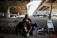 "A man who called himself ""J.R."" sat with his belongings outside the now-gated Tent City in May in Dallas. J.R. said he had been living in Tent City for two months. (G.J. McCarthy/The Dallas Morning News)"