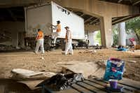 A crew from Green Planet Recycling prepared to clean up a homeless encampment Tuesday near downtown Dallas. The camp, located underneath Interstate 30 at Haskell Avenue, is the latest of its kind to be closed by the city. (G.J. McCarthy/The Dallas Morning News)