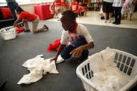 Jaylen Simpson, 8, gathers clothes during a laundry game at a celebration of Conn's HomePlus giving a washer and dryer to clean students' uniforms at Roger Q. Mills Elementary in Dallas on October 20, 2016. (Nathan Hunsinger/The Dallas Morning News)(Staff Photographer)