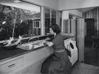 "<p>Jeanette Prinz cooks in the family kitchen in this 1950s photograph (the clothes washer is to her right). ""He [Harold Prinz] designed the large window in the kitchen so I could look out and watch the birds while I was making dinner. And I liked the openness of the house,"" she said in 2008. ""You didn't have to go through a lot of doors to get where you wanted to go. It's easy to handle, easy to clean."" Today, the kitchen retains its retro galley layout, but gets a decided upgrade in cabinetry and appliances. (Ulric Meisel/Special Contributor) </p>"