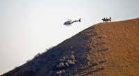 Three people on horseback watched from a hillside as a helicopter swept by a camp where pipeline protesters were gathered. (Tom Stromme/The Bismarck Tribune)