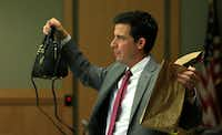 Defense attorney Cody Skipper holds up Anna Moses' purse that was found in the garage next to her body. It had $300 in cash. But police did not find the credit card she used to purchase a quesadilla.(Jae S. Lee/Staff Photographer)