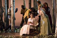 """The sisters Tatyana (Svetlana Aksenova, seated) and Olga (Kai Ruutel, bending over her) are contrasted in the Dallas Opera's dress rehearsal of """"Eugene Onegin"""" at the Winspear Opera House. (Rex C. Curry/Special Contributor)(Special Contributor)"""