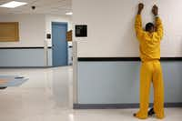 A juvenile inmate places his hands against the wall for a routine search at the Henry Wade Juvenile Justice Center in Dallas.<br>((Rose Baca/Staff Photographer))