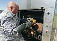 Ricky Kleibrink moves a chicken on racks in his outdoor oven.(Nathan Hunsinger/Staff Photographer)