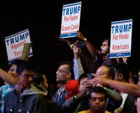 Supporters of Republican presidential candidate Donald Trump hold up signs as he speaks during a charity event hosted by the Republican Hindu Coalition, Saturday, Oct. 15, 2016, in Edison, N.J. (AP Photo/Julio Cortez)(AP)