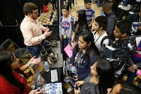 Alex Perales (top left) and Natalia Espino (bottom left) talk about engineering to students from John Adams Middle School as a part of the My Future My Way exhibit in Grand Prairie.(Nathan HUnsinger/The Dallas Morning News)