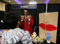 Austin Elliott (center) talks to Larry Hernandez about the Grand Prairie ISD dentistry program during an exhibit at Asia Times Square in Grand Prairie. (Nathan Hunsiinger/The Dallas Morning News )