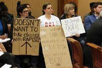 Members of the audience held signs during a board of visitors meeting about sexual assault at the University of Virginia in 2014 in Charlottsville, Va.  (File Photo/The Associated Press)