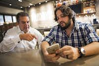 Ben Lamm, CEO and cofounder of  Conversable, (right) and Sherif Mityas, VP of strategy and brand initiatives for TGI Friday's, test out the restaurant chain's chatbot.(Smiley N. Pool/Staff Photographer)