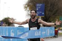 Logan Sherman crosses the finish line to win the 2015 Dallas Marathon.(<p>Staff photographer: Andy Jacobsohn</p>)
