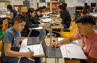 Andy Noyola (left) and Eric Diaz work on posters listing presidential candidate platforms during a class at Irving High School on Monday. (G.J. McCarthy/The Dallas Morning News)