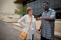 Sarah Bartfield (left) smiles as she waits with James Williams before he goes in to vote on Nov. 4 at the J. Erik Jonsson Central Library Friday in downtown Dallas. Williams, 45, voted for the first time in his life this year after being encouraged to do so by Bartfield, a co-worker at Temple Emanu-El. (G.J. McCarthy/Staff Photographer)