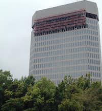 Work crews are still removing the exterior on the upper floors of the 400 Record building downtown.(Steve Brown)