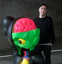 "Brooklyn-based artist Brian Donnelly, better know by his alias, KAWS, with his ""Companion"" (Resting Place) at a major survey exhibition of his work, ""KAWS: Where the End Starts,"" at the Modern Art Museum of Fort Worth. (Nan Coulter/Special Contributor)"