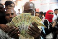 An Indian man holds up old versions of the 500 rupee denomination note as people queue inside a bank to deposit 500 and 1000 Indian rupee notes in Rahimapur village on the outskirts of Allahabad on November 10, 2016. (AFP/Getty Images)