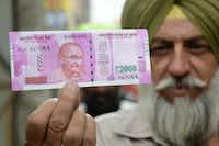 An Indian Sikh man displays a new 2000 rupee note at a bank in Amritsar on November 10, 2016.  Long queues formed outside banks in India as they reopened for the first time since the government's shock decision to withdraw the two largest denomination notes from circulation. (AFP/Getty Images)
