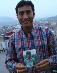 The adult Carlos holds up a photograph of himself as a child in Guatemala.(Steve Spriggs/Compassion International)