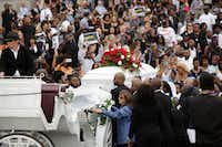 People gather around the coffin of Philando Castile, who was shot by police in Falcon Heights, Minn., as it's carried by a horse-drawn carriage during his funeral outside the Cathedral of Saint Paul in St. Paul, Minn., July 14, 2016. (Joshua Lott/The New York Times)