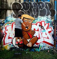 Dallas artist Jeremy Biggers cleared his spray can as he painted a caricature of President-elect Donald Trump during Go Paint Day. It was only his third time working with a spray can, he said.  (Tom Fox/Staff Photographer)