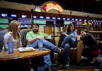 (From left) Laura Auwarter, Gus Olsen, Trinh Nguyen and Kim Hoang hang out at Main Event in Frisco, Texas. The employees from Plano-based Evantage, Inc. try to spend time with one another each Monday night, outside of the office, to build camaraderie and blow off steam. (G.J. McCarthy/The Dallas Morning News)(Staff Photographer)