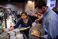 Melissa Harp (center) and Michael Wash serve themselves lunch at Pioneer Natural Resources' cafeteria at company headquarters in Irving. The buffet lunch is provided to employees free of charge. (G.J. McCarthy/The Dallas Morning News)(Staff Photographer)