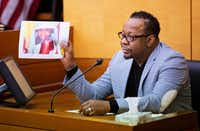 Bobby Brown holds up a picture of his daughter, Bobbi Kristina Brown, during a wrongful death case against her partner, Nick Gordon, in Atlanta, Thursday, Nov. 17, 2016. (AP Photo/David Goldman, Pool)(AP)