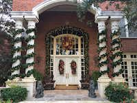 Exterior features like these tall columns wrapped in a wide garland draw attention to a doorway.(<p>(Holiday Warehouse)<br></p><p></p>)