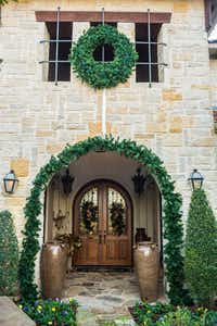 A wide, bold garland on a stone archway, along with a coordinating wreath, creates a timeless statement and defines the entrance to this home.(<p>(Clint Brewer)<br></p><p></p>)
