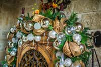 A garland with white and gold ornaments adorns a wine closet tucked under a covered porch.(<p>(Clint Brewer)<br></p><p></p>)