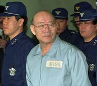 In this Feb. 26, 1996 file photo, former South Korean President Chun Doo-hwan enters the Seoul Court House dressed in prison garb for his first trial on corruption charges. (AP Photo/Yun Jai-hyoung, File)(AP)
