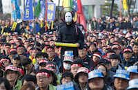 In this Saturday, Nov. 19, 2016 photo, a South Korean protester wearing a mask listens to a speech during a rally calling for South Korean President Park Geun-hye to step down in Seoul, South Korea. For the fourth straight weekend, masses of South Koreans were expected to descend on major avenues in downtown Seoul demanding an end to the presidency of Park, who prosecutors plan to question soon over an explosive political scandal. (AP Photo/Ahn Young-joon, File)(AP)