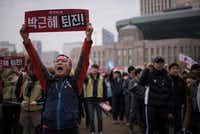 A protester holds a placard erading 'Park Geun-Hye resign!' during an anti-government protest at Seoul city hall plaza on November 19, 2016. Up to half-a-million protestors were expected to take to the streets of Seoul for the fourth week in a row, demanding President Park Geun-Hye resign over a corruption scandal.(AFP/Getty Images)