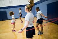 Najla Dreca (left), Alexandra Walton (center left), Mayme Fanning (center), and Caitlyn Collins do jump-rope workouts during seventh-grade PE class at Cockrill Middle School in McKinney. (Ting Shen/The Dallas Morning News)