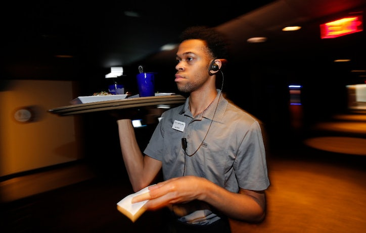 austin murray delivers the food to the customers at studio movie grill