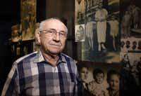 Max Glauben in front of some of the photographs taken of him and his mother and brother in Poland at the Dallas Holocaust Museum/Center for Education.((David Woo/Staff photographer))