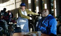 Johnson dances for guest Frank Pineset. The cafe serves about 1,000 people daily, seven days a week.(Nathan Hunsinger/Staff Photographer)