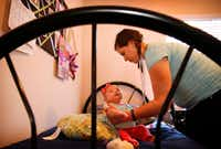 Desiree Wilber finishes changing Lillian's diaper in her private bedroom at Santa Maria Hostel in Houston. (<p>(Tom Fox/Staff Photographer)<br></p><p></p>)