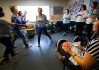 """Jamie Lehew feeds her baby Lincoln (right) as Amber Bolanos (center) and her fellow mothers practice a skit to Katy Perry's song """"Rise"""" in preparation for BAMBI's performance at the peer advisory monthly program at Santa Maria Hostel in Houston. (Tom Fox/Staff Photographer)(<p><br></p><p></p>)"""