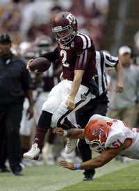 Texas A&M quarterback Johnny Manziel (2) leaps as Sam Houston State linebacker Eric Fieilo (51) hits him out of bounds during the first quarter of an NCAA college football game Saturday, Sept. 7, 2013, in College Station.(AP Photo/David J. Phillip)