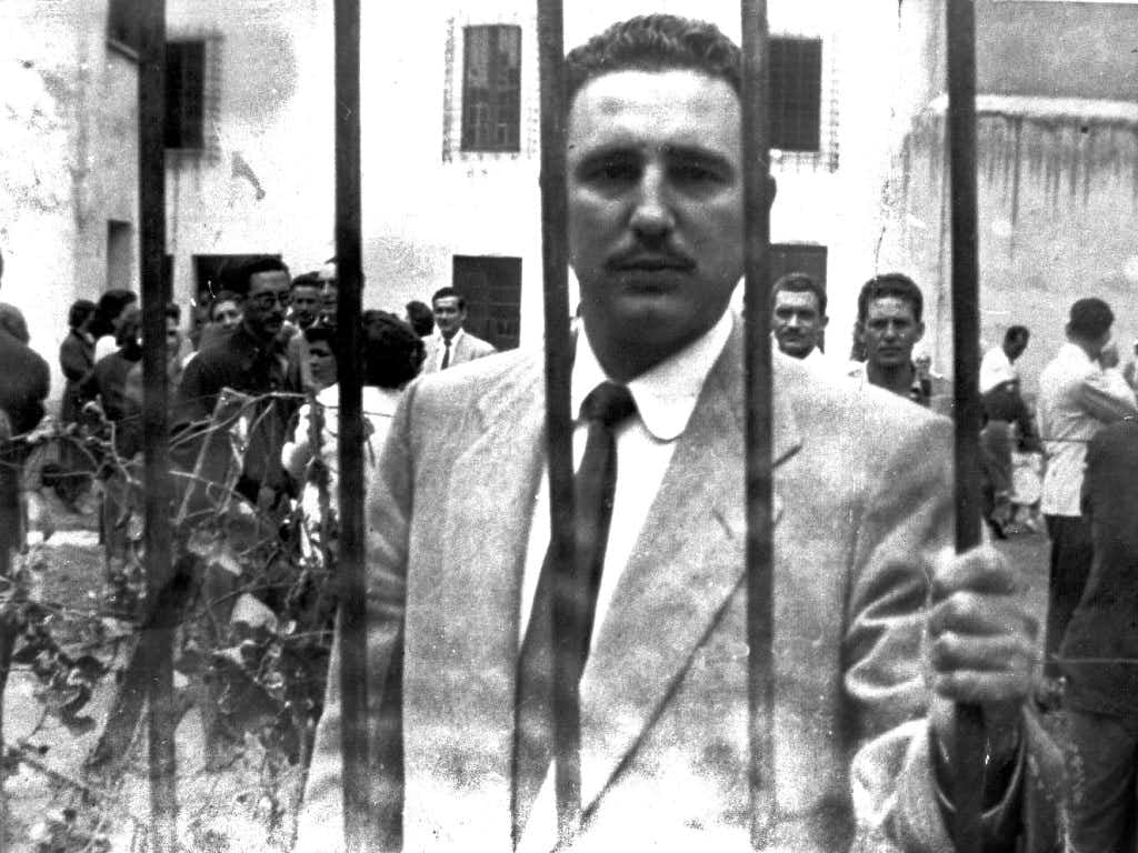 This handout photo provided by the Oficina de Asuntos Historicos del Consejo de Estado and taken on Jan. 1, 1956, shows Fidel Castro standing behind bars at the Miguel Schultz prison in the Mexican colony of San Rafael after being arrested by the Mexican Police with the cooperation of  then-president of Cuba Fulgencio Batista. /AFP/Getty ImagesAFP/Getty Images