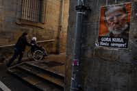 A man wheels a woman in a wheelchair near to a poster with the image of former Cuban President Fidel Castro reading, ''Long Live for Cuba. For Ever,'' after his death was announced on Friday, in Pamplona, northern Spain. (AP Photo/Alvaro Barrientos)(AP)