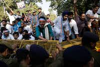 Members of the National Students Union of India (NSUI), student wing of India's main opposition Congress party, try to cross barricades during a protest against the government's decision to withdraw high denomination notes from circulation, in New Delhi, India, Monday, Nov. 28, 2016. (AP Photo/Tsering Topgyal)AP