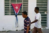 People passed a Cuban flag gathered with a black ribbon, a sign of mourning, in the town of Regla, across the bay from Havana, on Sunday. (Ramon Espinosa/The Associated Press)