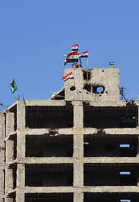 Syrian flags flutter on top of a building in Aleppo's Bustan al-Basha neighbourhood on November 28, 2016 during the Syrian pro-government forces assault to retake the entire northern city from rebel fighters. AFP/Getty Images