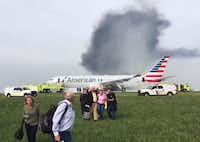 Passengers were assisted away from a burning American Airlines jet that aborted takeoff and caught fire on the runway at Chicago's O'Hare International Airport on Friday. (Jose Castillo)