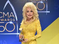 In this Nov. 2, 2016 file photo, Dolly Parton poses in the press room with the Willie Nelson Lifetime Achievement Award during the 50th annual CMA Awards in Nashville, Tenn. (Photo by Evan Agostini/Invision/AP, File)AP
